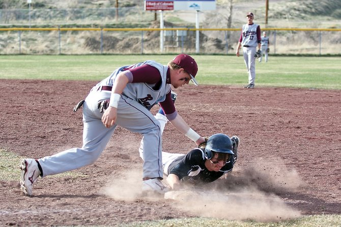Scott Costello safely dives back to first base during the first game of Moffat County High School doubleheader against Palisade High School on Friday at Craig Middle School. MCHS won the first game, 12-10.