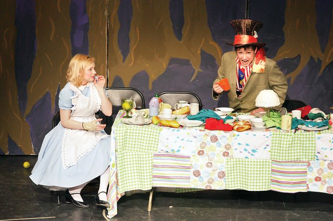 "Emily Miller, playing Alice, and Cody Fallon, as the Mad Hatter, enact a tea party during the opening night of Moffat County High School's spring production of ""Alice in Wonderland"" on Thursday in the MCHS auditorium. The final two performances take place at 11 a.m. and 6:30 p.m. today."