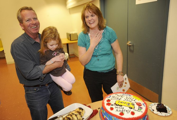 Luke Norland and his daughter, Kelsey, visit with outgoing Heritage Park Preschool Director Audrey Zwak as she reacts to seeing a cake baked for her goodbye celebration Thursday at the school.