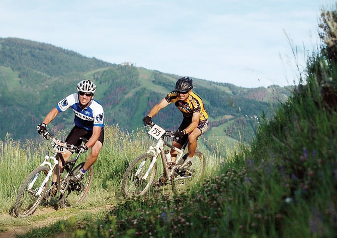 Sars Larson, left, and Rick Hager race at a Town Challenge race last summer on Emerald Mountain with Mount Werner in the background.