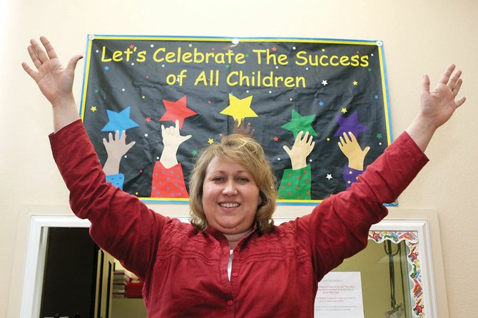 Sarah Hepworth, currently the head of the Moffat County School District Early Childhood Development Program, stretches her arms in the air for this portrait Friday at the school district preschool. Hepworth was appointed principal of East Elementary School during Thursday night's school board meeting.