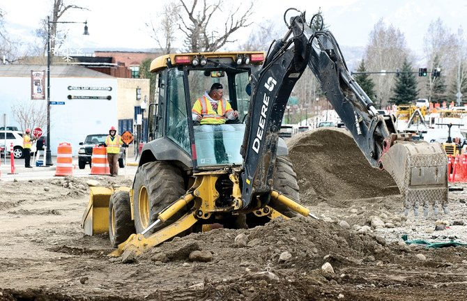 Jesus Casillas uses a backhoe to tear out the curb along Lincoln Avenue on Monday afternoon in downtown Steamboat Springs. Crews were preparing to resume paving last night.
