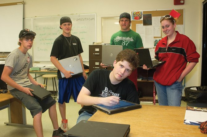 Five Hayden seniors were given refurbished laptops as part of a program to provide laptops to graduating seniors who plan to continue their education in college next year. Among the seniors who took advantage of the new program this year were Ryan Mahaffie, center, and, from left, Wayne Dubs, Dylan Sather, Koleman Williams and  Samantha Huffar.