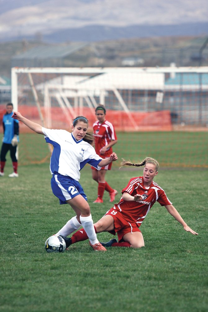 Steamboat Springs High School senior McKenzie Worden slides in to take the ball away from a Moffat County High School attacker during a game Tuesday at Woodbury Park. The Sailors won, 4-0.