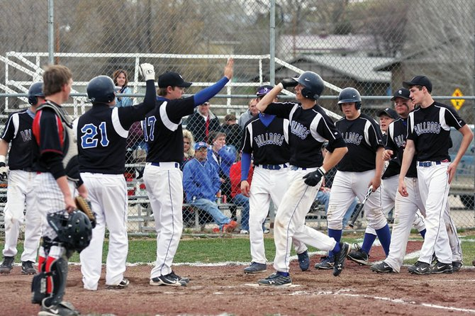 Scott Costello, right, slaps hands with teammates while crossing home plate after hitting a home run on Tuesday, at Craig Middle School. The Bulldogs beat the Steamboat Springs High School Sailors, 9-3, behind home runs from Costello, Dylon Camilletti and Bubba Ivers.