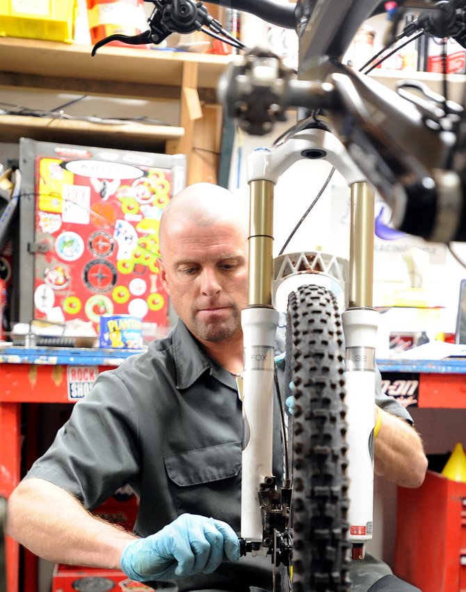 Chris Johns works to repair a bike Wednesday at his Wheels Bike Shop in Steamboat Springs. Wheels will join with the other three local bike shops May 8 to host bike safety and skills booths at the Bike Fest in Steamboat.