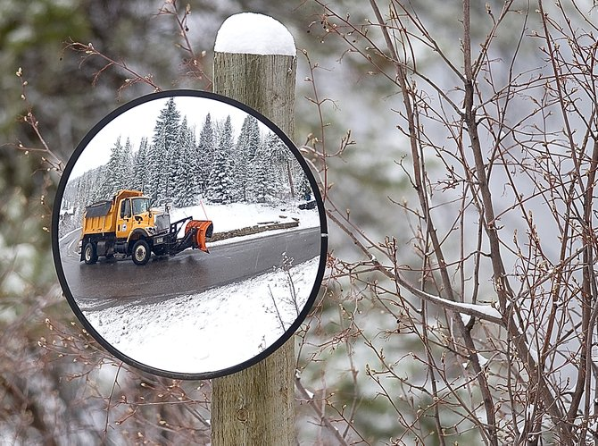 City equipment operator Jason Roiko's plow truck is reflected in a mirror as he drives past a sharp corner of Burgess Creek road  Thursday morning. City plows were back out after a spring storm dumped several inches of snow in the area. More wet weather is expected during the weekend.