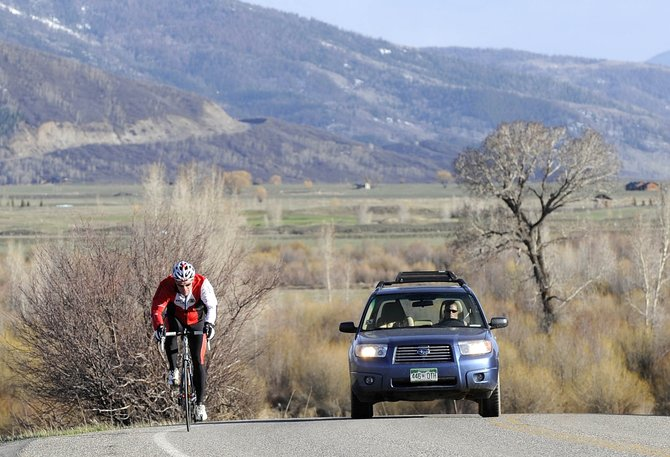 Part-time Steamboat Springs resident Pat McGaughran takes an early evening ride Tuesday along Routt County Road 14.  About $1,500 soon will be spent on a public education campaign to encourage respect among drivers, bicyclists and other users of county roads.