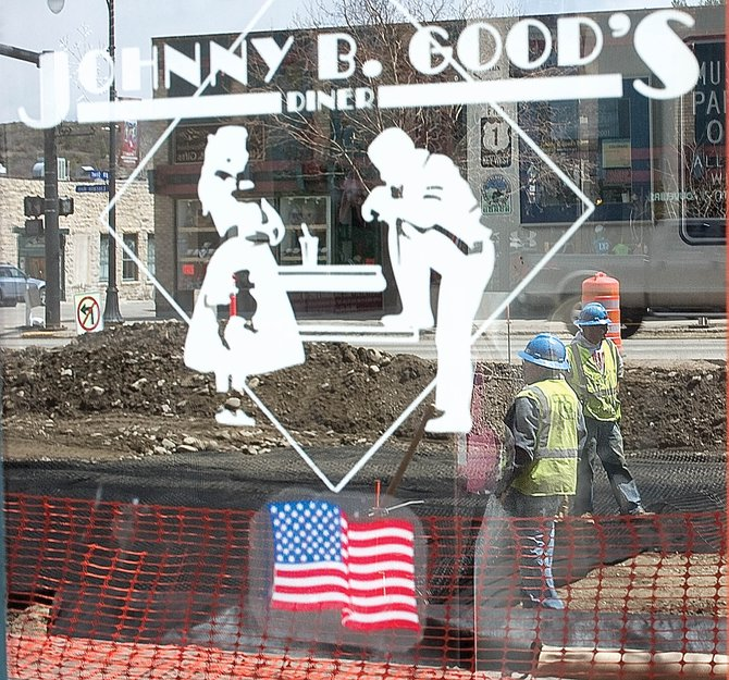 Construction workers are reflected in the window of Johnny B. Good's Diner in downtown Steamboat Springs on Wednesday. The Steamboat Springs Chamber Resort Association and Mainstreet Steamboat Springs are planning several upcoming downtown promotions, including Restaurant Week at the end of this month.