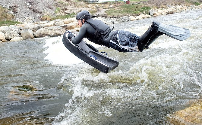 Danny Tebbenkamp leaps into the waters of the Yampa River on Wednesday while riverboarding behind the Bud Werner Memorial Library.