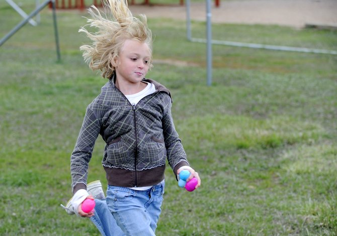 Hayden Valley Elementary School fifth-grader Mallory Ormesher runs Tuesday with her Easter eggs containing prizes rewarded for being good in class. The treasure hunt was an incentive for the students participation in the schools Positive Behavior Support program.