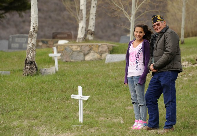 Steamboat Springs Middle School seventh-grader Reina Salky and Jim Stanko, commander of Steamboat's American Legion Post No. 44, stand near a wooden cross at the Steamboat Springs Cemetery. Reina is raising money to help replace the wooden crosses with a military headstone. Stanko began identifying the graves in 1995 and said Reina has raised $1,200 of the $1,500 goal to pay for the headstones.