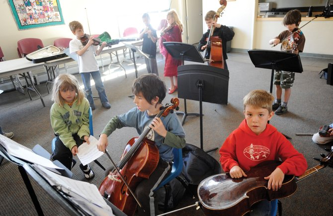 Lowell Whiteman Primary School students, from left, Madison Knutson, Miles Borden and Camden Wilkinson attend music class Wednesday morning.