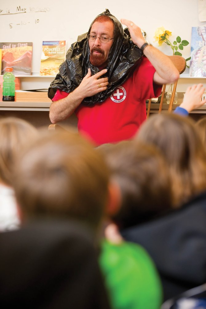 Darrel Levingston, of Routt County Search and Rescue, demonstrates how a plastic bag with a hole cut in it can help if you get lost in the backcountry. Levingston was making a presentation to a class at Strawberry Park Elementary School on Monday aimed at young students and what to do if they get lost in the backcountry.