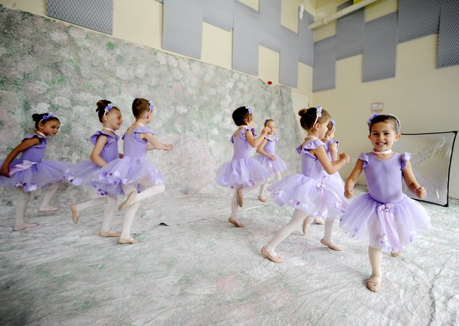 "Suzy Magill, 5, right, dances around before having her picture taken Wednesday. Suzy is part of the group ""Magic Tutus,"" which will perform at the annual Rocky Mountain Dance recital at 6:30 p.m. today and Saturday."