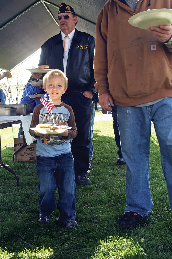 Kristopher Walker, 5, walks down the buffet line during the annual Hometown Heroes Community Picnic on Saturday at Craig City Park. The event honored active military members in Moffat County, along with past veterans.