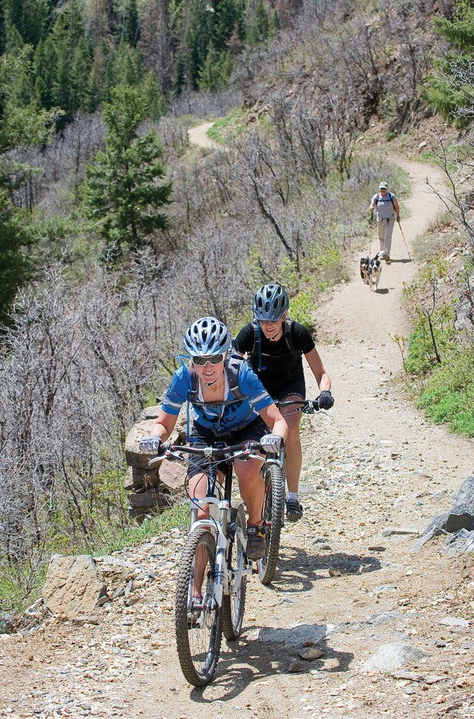 Cyclists Blair Seymour, front, and Kris Rowse ride up the Mad Creek Trail on Monday morning after passing hiker Susan Marshall and her dogs. Trails in Steamboat Springs are slowly becoming available to mountain bikers and hikers as the terrain in our area continues to dry out.