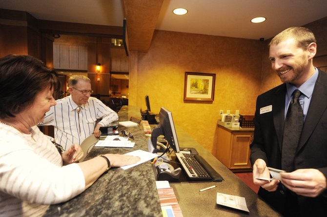 Ashley Rogers, front office manager for The Steamboat Grand, checks in Nancy and Garry Pittman, of Colorado Springs, on Thursday. Although 2009 was a bruising year for the resort hotel industry  lodging tax revenues dipped more than 23 percent in Steamboat Springs last year  David Belin, of the research and consulting firm RRC Associates, said Thursday that lodging demand is showing signs of a nationwide rebound this year and trending upward for the summer.