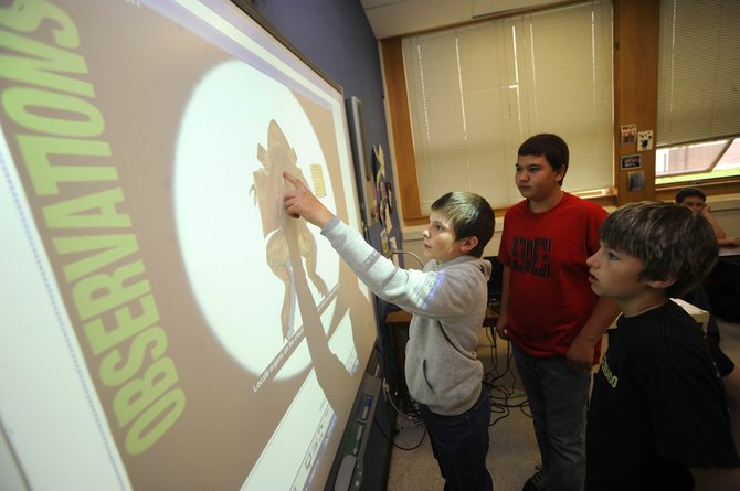 Hayden Middle School sixth-graders Garrett Camilletti, right, and Dean Wagner, left, watch Kenny Corriveau demonstrate Tuesday how the class has used a SMART Board in the classroom.