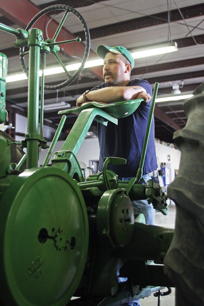 Doug Willems leans against the seat of a 1939 John Deere Model B tractor Saturday at Precision Auto Service. Willems and his cousin, Drew Chamberlain, were at the shop getting tractors their late grandfather restored ready for the Grand Olde West Days Antique Tractor Pull this weekend.