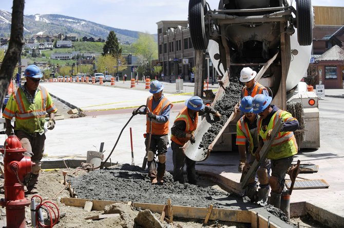 Scott Contracting workers pour concrete Tuesday at Seventh Street and Lincoln Avenue.