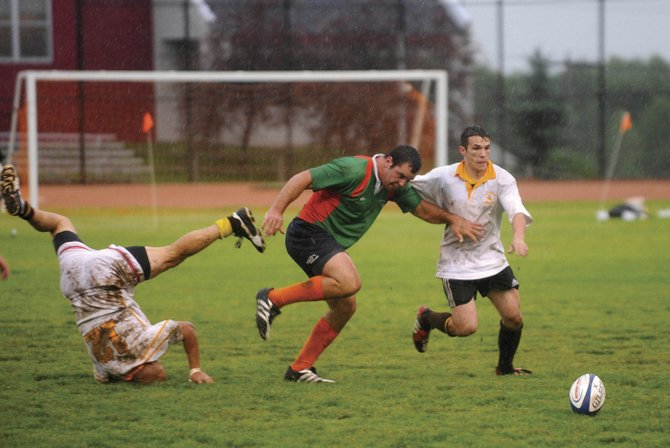 Steamboat Springs rugby player Chris Baumann, center, challenges two Wyoming players during the 2009 Cow Pie Classic Rugby Tournament championship game. The rugby club will kick off its season this year June 12 at Vail.