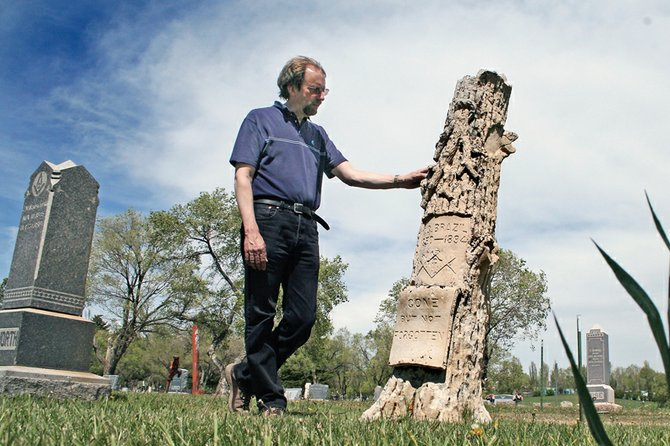 Dan Davidson, director of the Museum of Northwest Colorado, stands near the gravestone of Christopher C. Brazil at Craig Cemetery. Davidson found an old photo of Brazil's grave decorated for Memorial Day in May 1896, which spurred his research into Brazil's life.