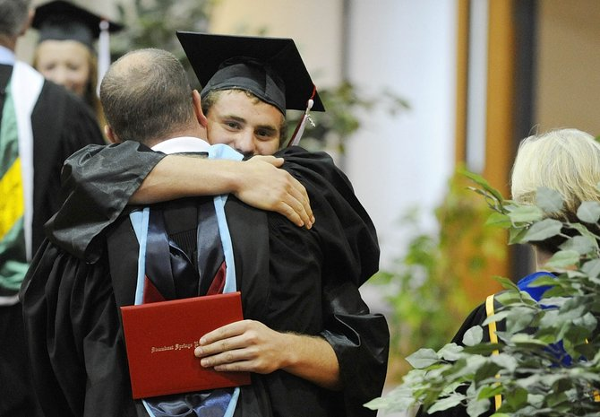Mitch Lekarczyk hugs Steamboat Springs High School principal Kevin Taulman after receiving his diploma during Saturday's ceremony.