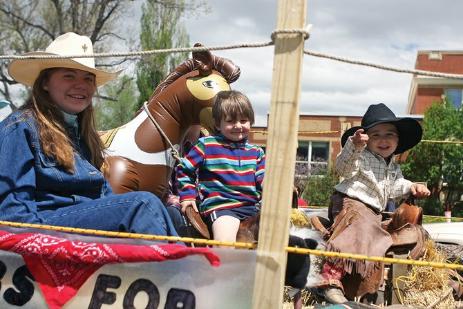 Julianna Sheeran, 19, Joseph Byram, 3, and Ryan Wells, 2, ride on the Calvary Baptist Church float during the Grand Olde West Days parade Saturday on Yampa Avenue.