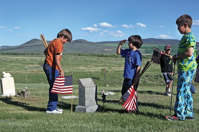 Sebastian Hadley, 7, salutes while Hunter Roberts, 11, places a flag Sunday night at Craig Cemetery in preparation for today's Memorial Day service. Mikey Bingham, 11, far right, and Thomas Baker, 10, in the background, also volunteered to help set flags by veterans' headstones.