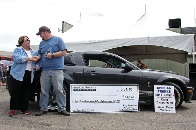 Pam Foster congratulates Opie Smith for winning the Grand Olde West Days car show with his 2007 Shelby GT500 on Monday in the Mather's Bar parking lot. Smith said he found the vehicle through eBay and picked it up in Maryland.