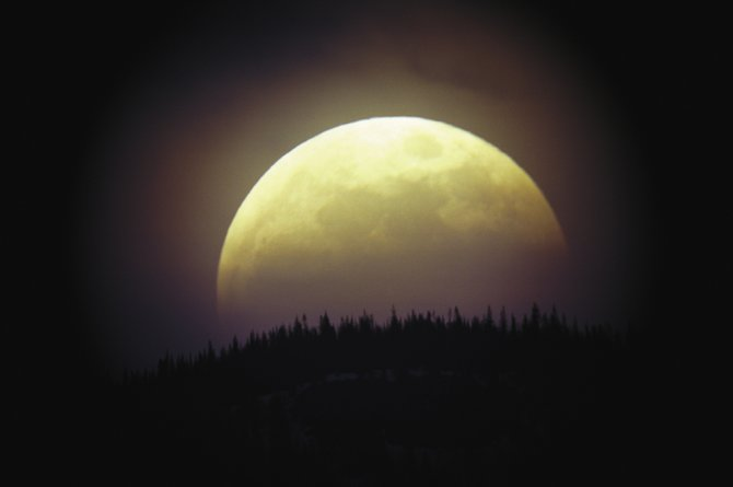 When the full moon sets at dawn on the morning of June 26, half of it will be engulfed in the shadow of the Earth. The scene will resemble this image of the partially eclipsed moon rising at dusk May 15, 2003. The moon will be totally eclipsed for Colorado this coming Dec. 21.