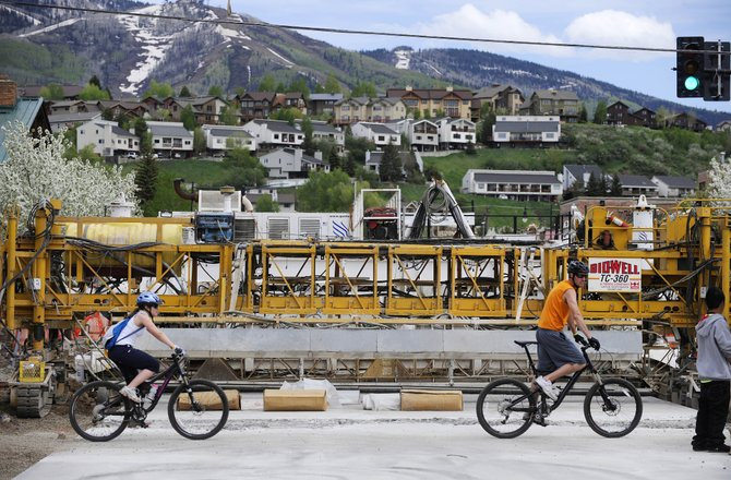 Steamboat Springs residents Michele Friedmann and Adam Heuerman ride their bikes Monday across Lincoln Avenue in front of paving equipment parked at Fifth Street. Officials hope to have the intersection reopened by the end of this week, in time for the Steamboat Marathon on Sunday.