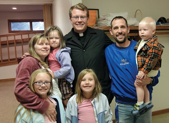 Father Randy Dollins of St. Michael Catholic Church poses with the Neton family of Craig at a reception in his honor Tuesday at the church. Dollins will depart Monday for Summit County after a three-year assignment in Northwest Colorado.