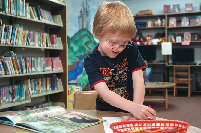 Avery Mac Phillips, 4, of Craig, alternates between coloring and reading a book Thursday in the children's room of the Craig branch of Moffat County Libraries. The library began its Summer Reading Program for all ages this week.