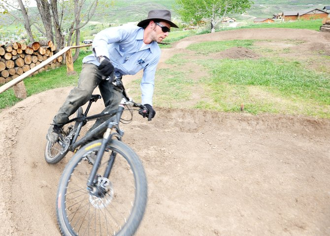 Stu Hassell rides on a pump track he built next to his home in Oak Creek.