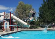 Samuel Walls, 10, does a back flip off the diving board during a sunny Friday at the Craig Swimming Complex. Walls just finished fourth grade at Sandrock Elementary School and said he's happy to enjoy the summer.