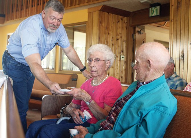 Pastor John Turner of Faith Lutheran Church hands snacks and drinks Friday morning to church founders Vera and Vern Herbert. The church will celebrate its 50th anniversary with events and services June 19 and 20.
