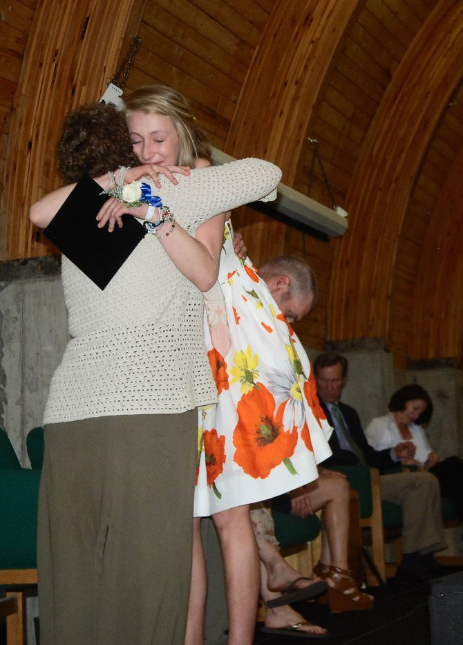 High school graduate Shane McLean hugs Margi Missling-Root, director of experiential education, during ceremonies Friday at The Lowell Whiteman School.
