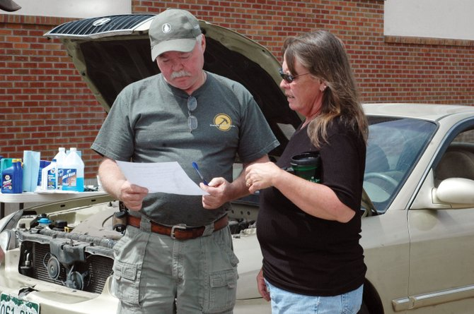 John Furman goes over a maintenance checklist he and several volunteers performed on Debbie Backle's car Saturday at the Love INC Car Care Clinic. The volunteers serviced 12 cars at the quarterly event at The Journey at First Baptist Church.