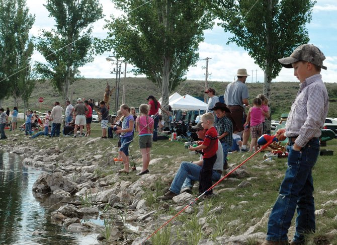 Michael Voloshin, 5, far right, waits patiently for a bite at the annual Huck Finn Cops and Kids Fishing Day. The Veterans of Foreign Wars Post 4265 and Ladies Auxiliary, local law enforcement agencies, and the Colorado Division of Wildlife organized the event, which drew about 100 children.