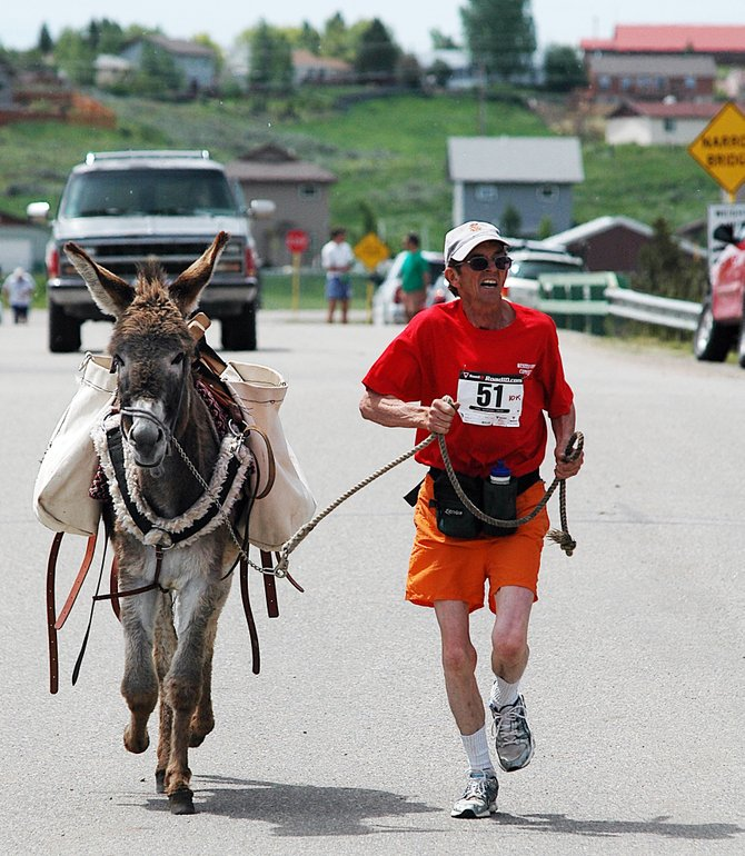 Tom Williams runs with his donkey, Justine, toward the finish line in the 10-kilometer run at the Cog Run in Hayden in 2009. The donkey (and Williams) finished the race in 1 hour, 29 minutes and 18 seconds.