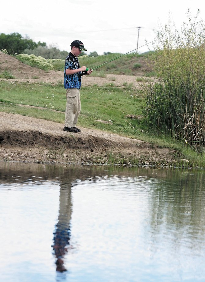 Zach Soron, 11 reels his fishing in during a dedication ceremony Thursday at the Little Rascals Pond. The project to improve the pond took five years.