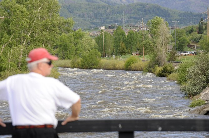 Bill Kahle, of Ohio, stands on the 13th Street bridge overlooking the Yampa River on Tuesday afternoon. Cooler temperatures are expected to cause water levels to decrease this weekend.