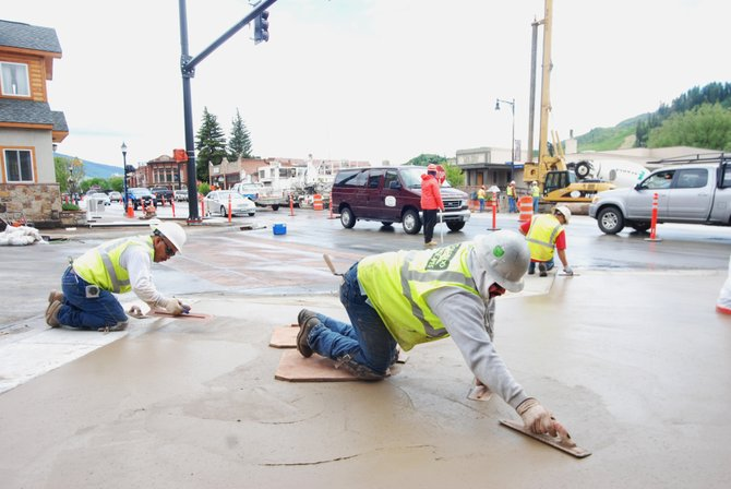 Antonio Gomez, front, of Colorado Hardscapes, smooths tinted concrete at Eleventh Street and Lincoln Avenue on Monday as traffic navigates the construction zone in downtown Steamboat Springs.
