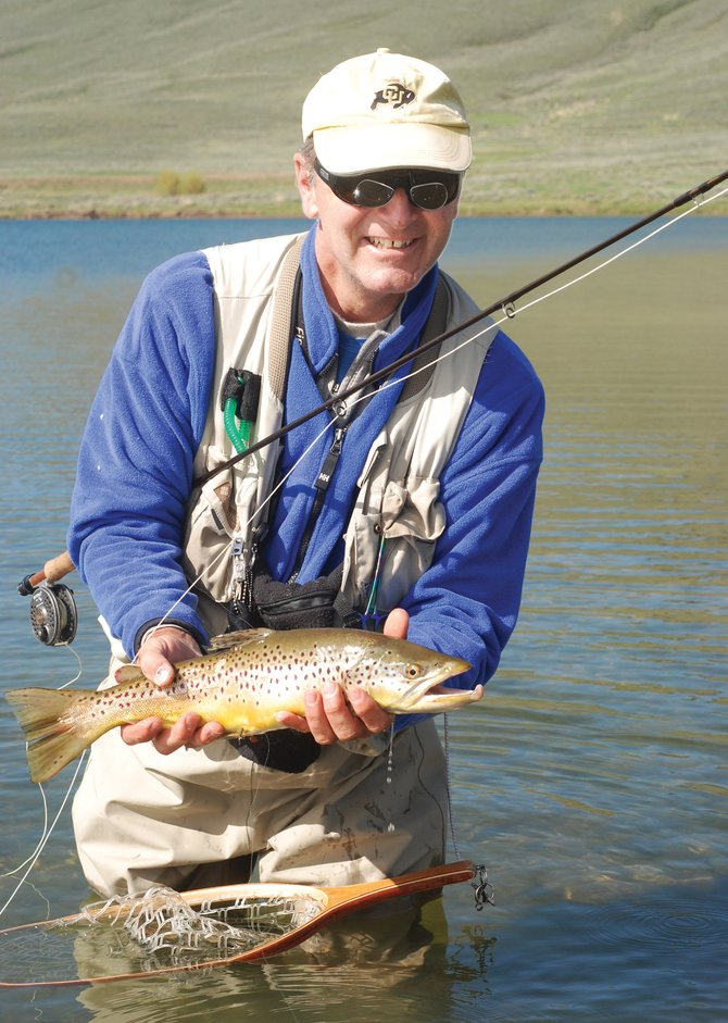 Jim Comeau shows off a nice brown trout caught on a nymph fly pattern at  North Delaney Buttes Lake on Saturday.