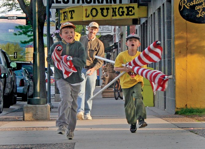 Joel Roberts, 7, left, races his brother Daniel, 8, to the nearest flagpole Monday night along Yampa Avenue in downtown Craig. The two helped take down 125 flags the Craig Rotary Club set up around Craig in honor of Flag Day.