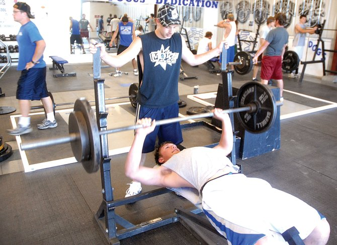 Sophomore Garrett Stewart, back, spots junior Dario Georgiou Tuesday at the Moffat County High School weight room. Stewart and Georgiou are both part of the MCHS football team, which works out every week at 7 p.m. Monday through Thursday.