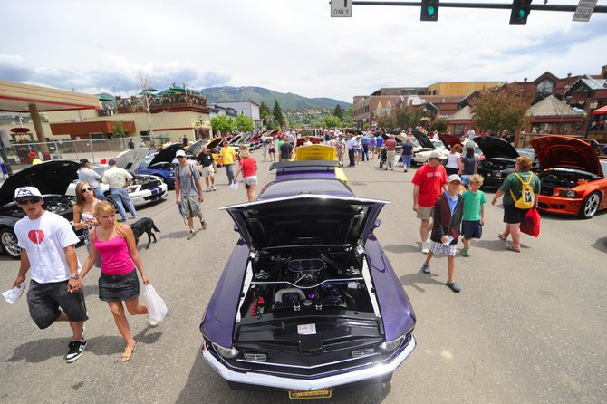Attendees of last year's Mustang Roundup Show 'n' Shine display check out the vehicles parked on Lincoln Avenue. Be on the lookout for Mustangs new and old this weekend