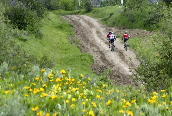Mountain bikers head toward the Emerald Mountain trails Wednesday afternoon. Beetle-kill mitigation efforts will shut down many upper-mountain singletrack trails.
